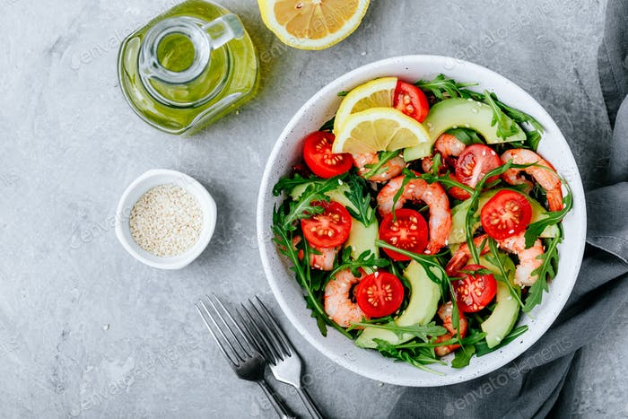 Healthy arugula salad bowl with shrimp, avocado, tomato, and sesame seeds on gray stone background.