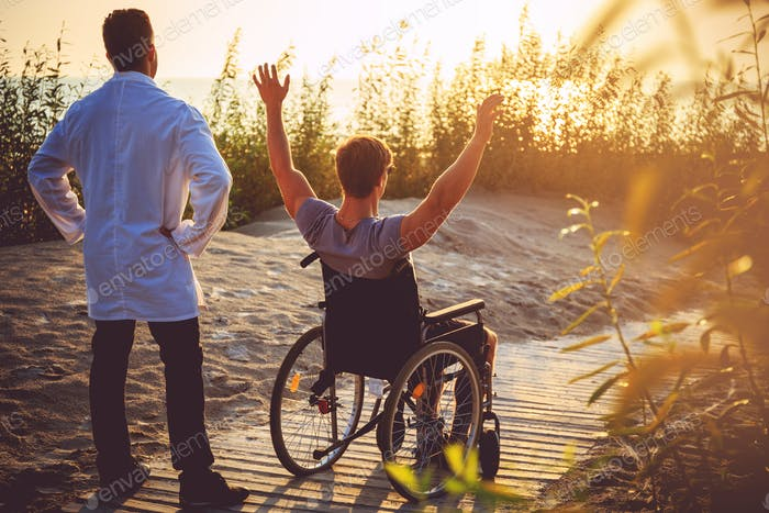 Ein Mann im Rollstuhl und seine Krankenschwester.