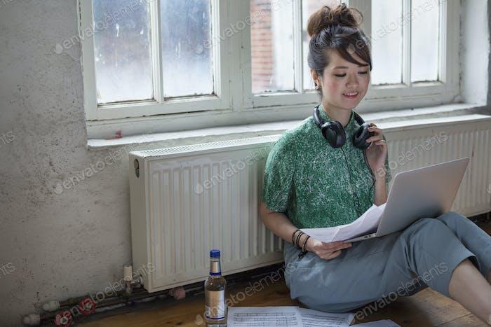 Junge Frau sitzt auf dem Boden in einem Probenstudio, mit einem Laptop-Computer, Blick auf Blatt