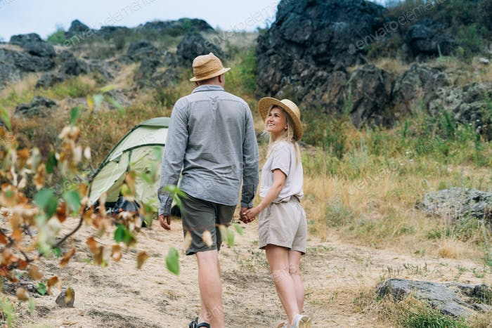 Happy young couple travelers in casual outfits with tent on mountain background