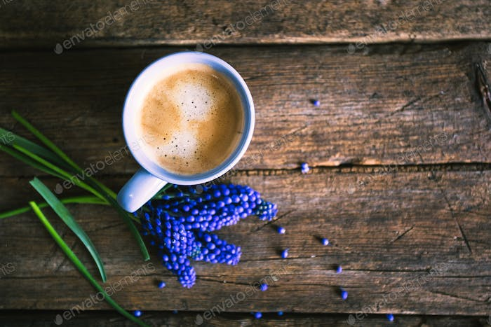 Blue flowers and a cup of coffee on a wooden background