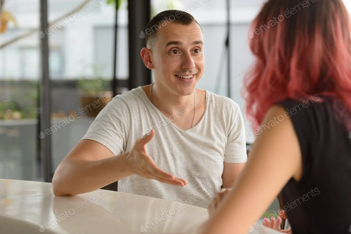 Portrait of happy handsome man talking to woman on the counter