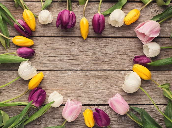 Heart shape made of tulips on wooden background, top view