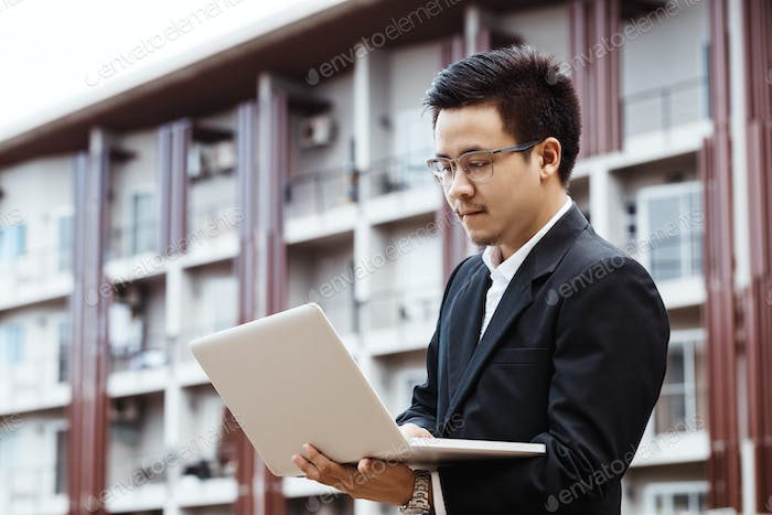 Concept Business - Handsome asian Business man working on property investment with laptop