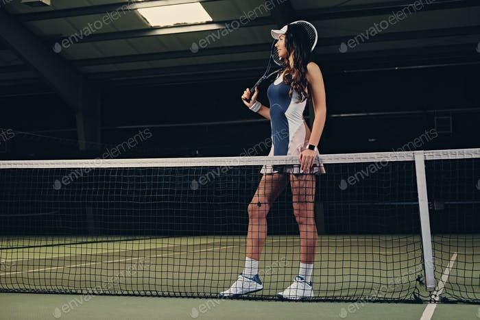 Female tennis player posing on an indoor tennis court.