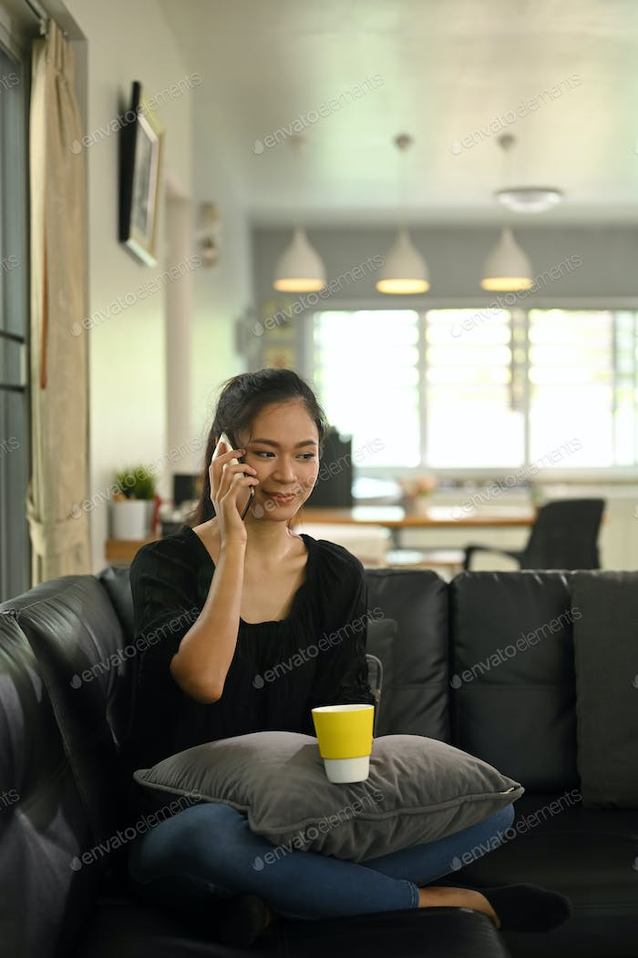 A young woman is talking on a telephone while sitting on a leather sofa.