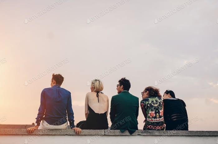 Junge Leute hängen auf dem Dach bei Sonnenuntergang