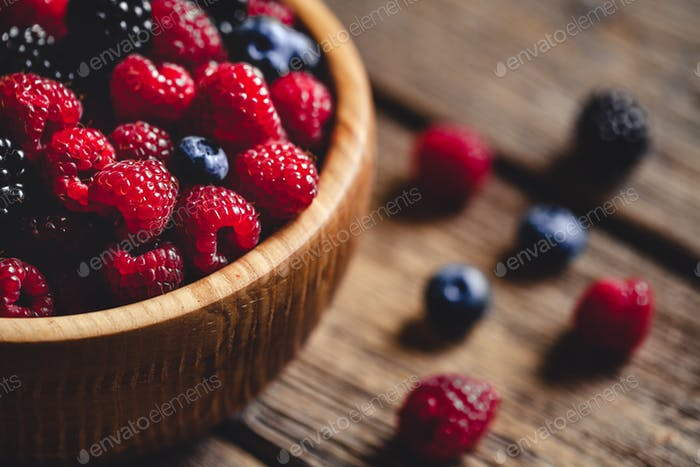 raspberries and blackberries on a wooden background in vintage style. Cutting board