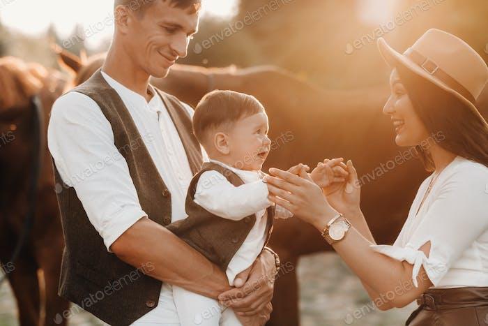 Eine Familie in weißen Kleidern mit ihrem Sohn zu Fuß mit zwei schönen Pferden in der Natur. Ein stilvolles
