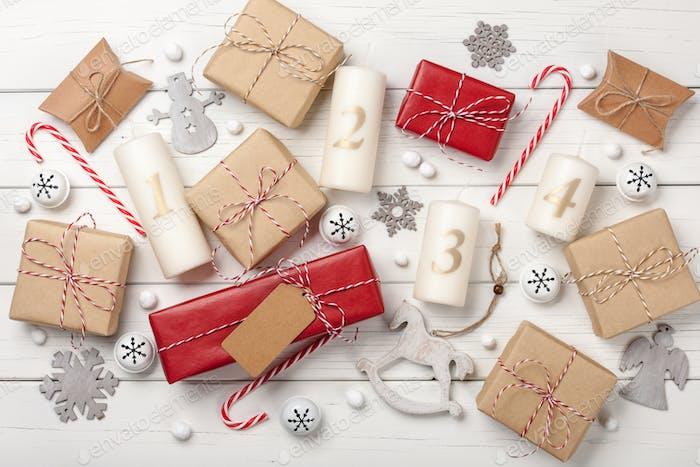 Adventskerzen, Weihnachtsdekoration und Geschenkboxen auf weißem Holzhintergrund