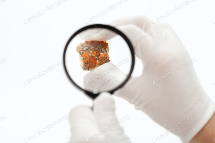 master inspects spessartine garnets with magnifier