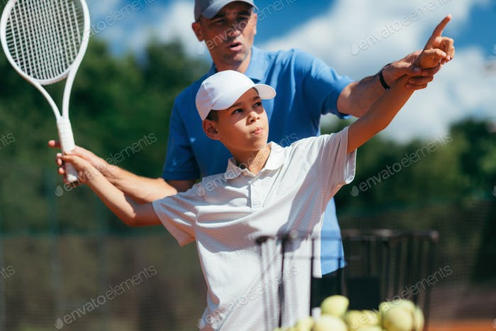 Tennis Instructor Practicing Service with Junior Athlete