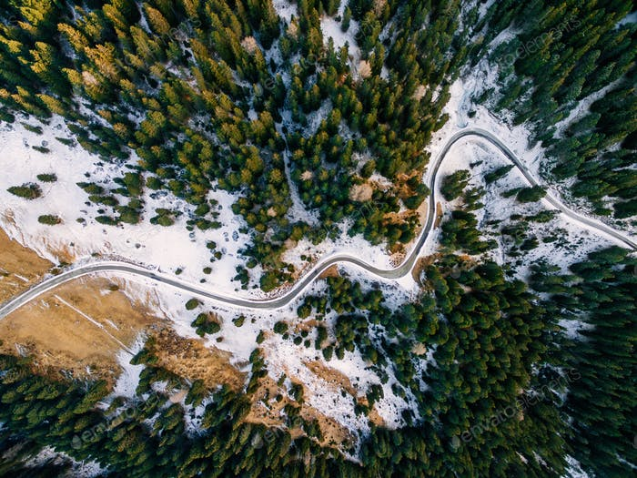 Aerial view of snowy forest with a road. Captured from above with a drone