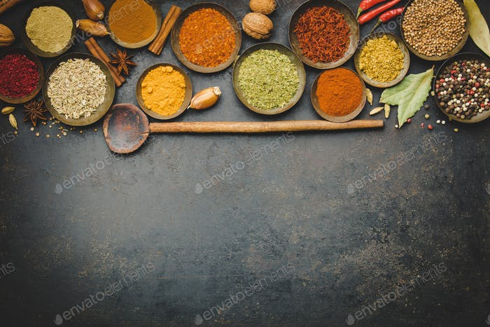 Various bowls of spices over dark background