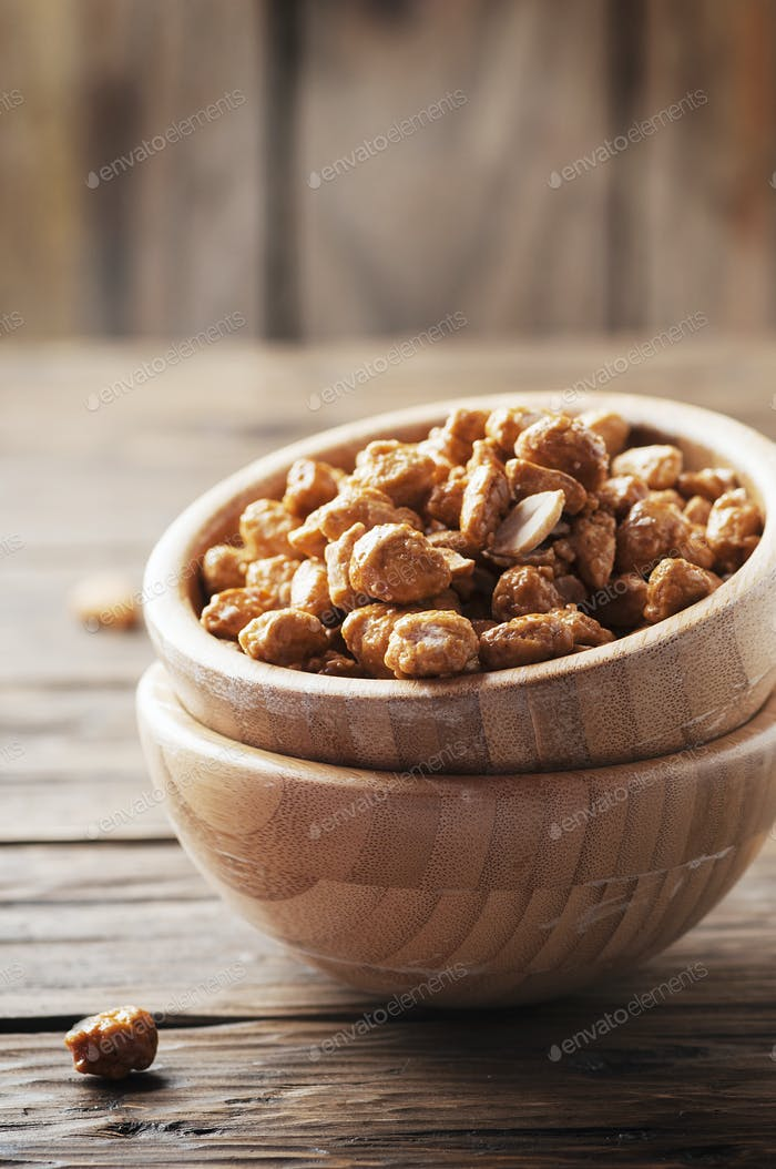 Sugared peanuts on the wooden background