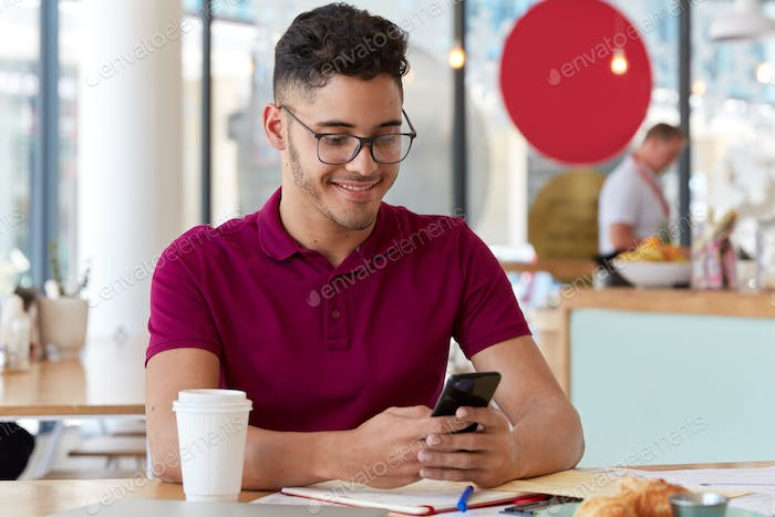 Satisfied freelancer works online, holds cellular, sends text message in social networks, sits in re