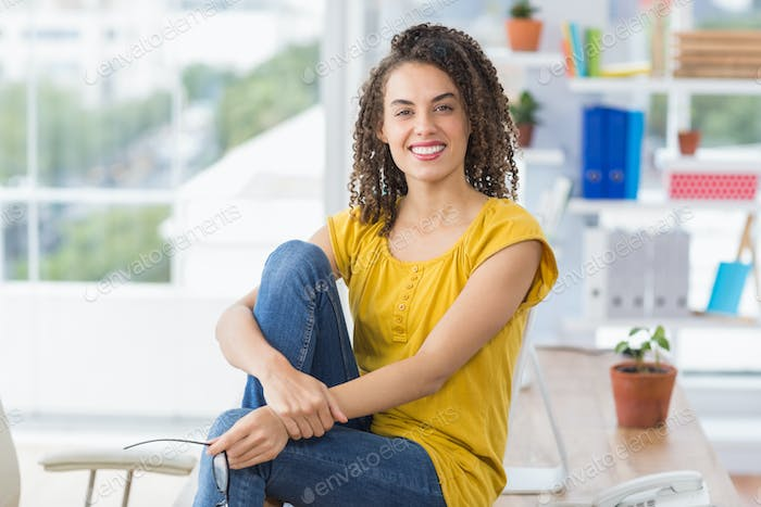 Smiling young businesswoman looking at the camera sitting on the table
