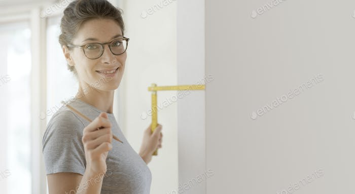 Smiling woman doing a home makeover and measuring with a ruler