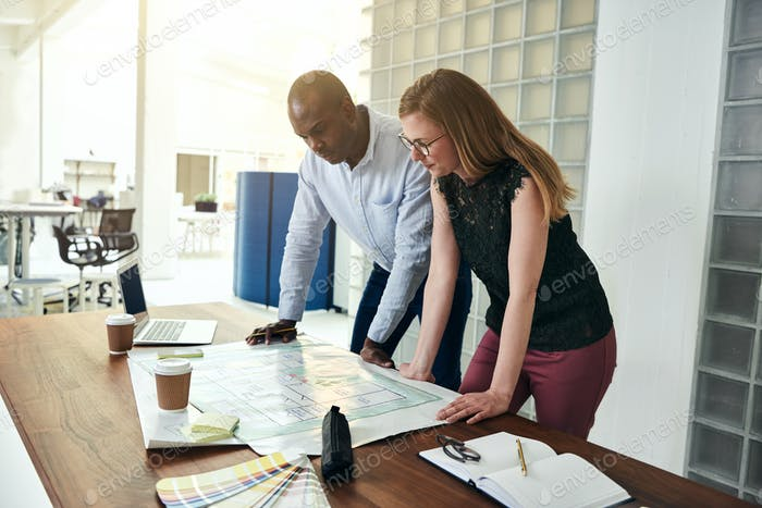 Two architects discussing a building design in an office