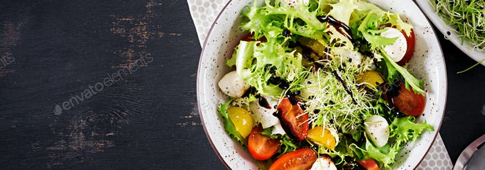 Vegetarian salad with cherry tomato, mozzarella and lettuce. Ita