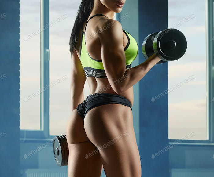 photo of strong fit model training in gym with heavy dumbbells