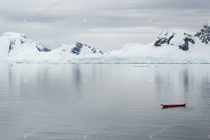 A small boat, a kayak on the flat calm waters off an Antarctic island shore.