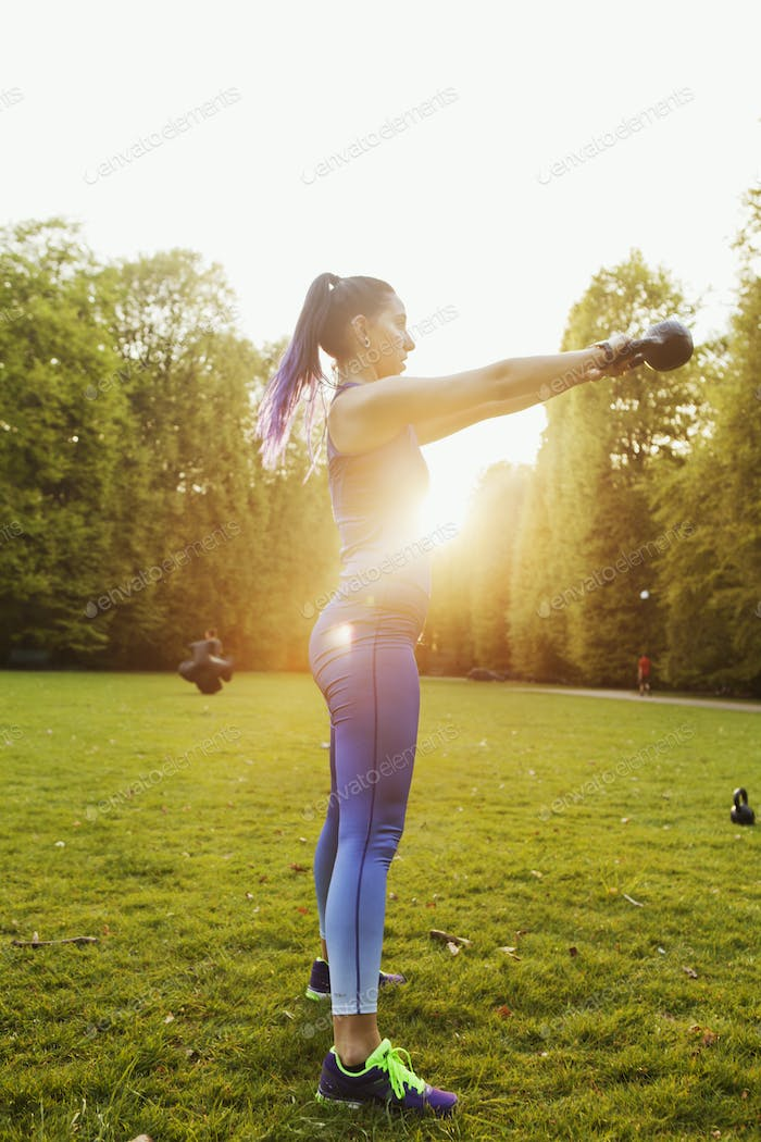 Young woman exercising with kettlebell standing on grassy field against clear sky