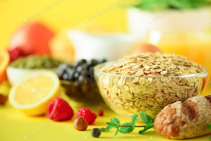 Oat flakes with milk, fresh berries, yogurt, boiled egg, nuts, fruits, orange, banana, peach for