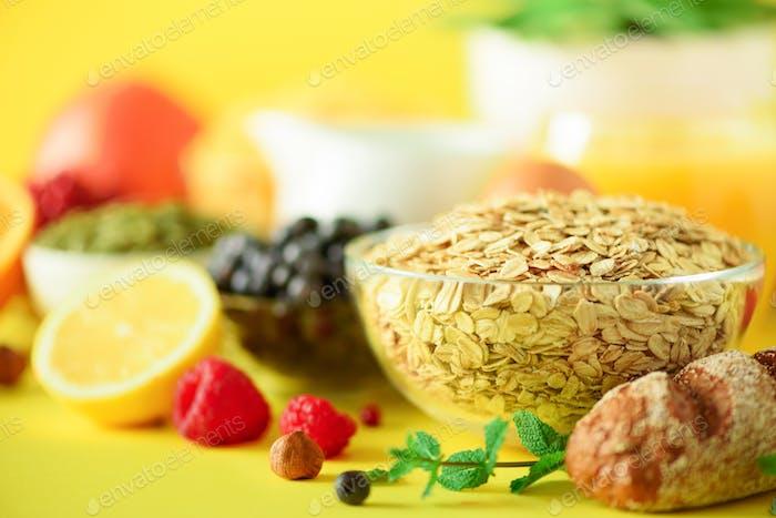Oat flakes with milk, fresh berries, yogurt, boiled egg, nuts, fruits, orange, banana, peach for