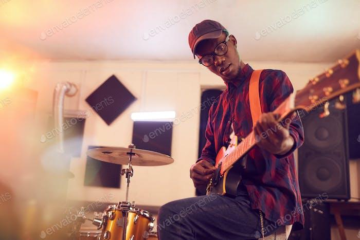 African Young Man spielt Gitarre bei Probe