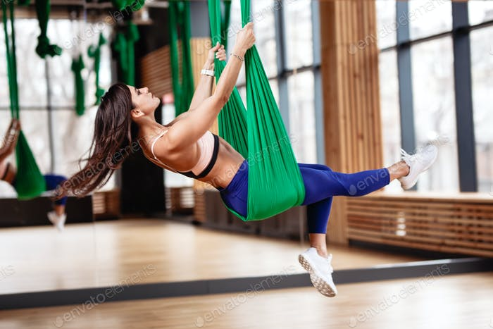 Beautiful young brunette girl is on the aerial silks next to the big mirror in the modern gym
