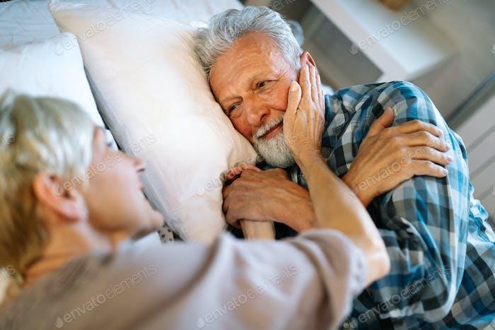 Happy senior couple embracing, sleeping together in bedroom
