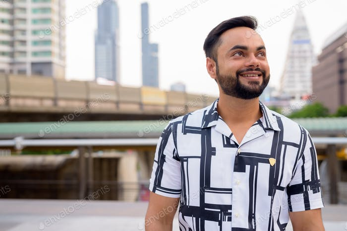 Happy young bearded Indian man thinking against view of sky train station