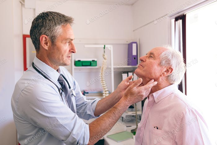Male doctor checking senior Caucasian man in clinic at retirement home