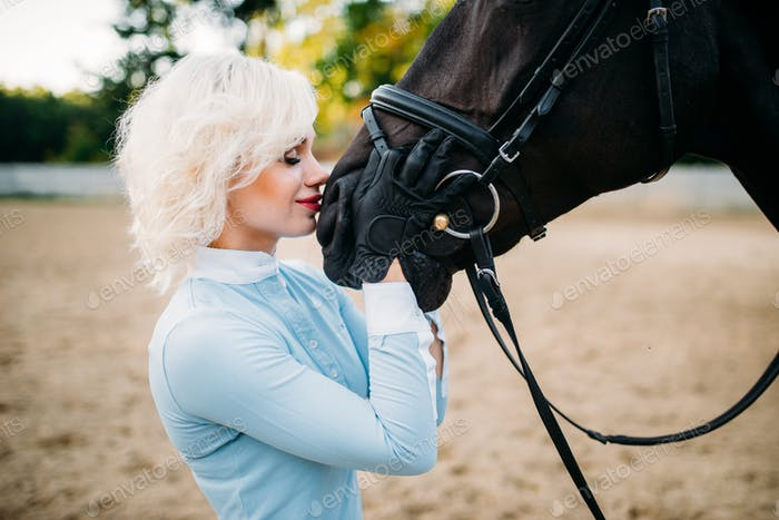 Woman hugs her horse, friendship, horseback riding