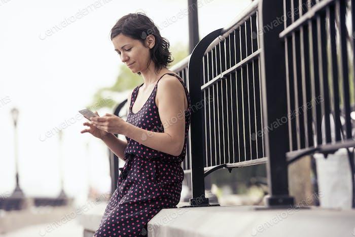 Eine Frau, die auf einer Straße pausiert, sitzt und ihr Handy überprüft.