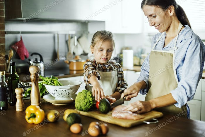 daughter helping mother in cutting vegetables