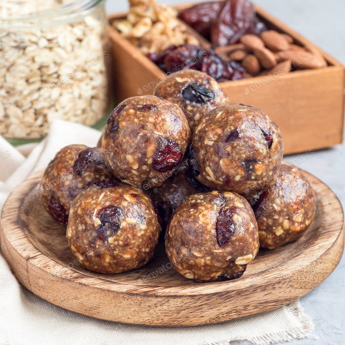Energy balls with cranberries, nuts, dates and rolled oats on a wooden plate, square