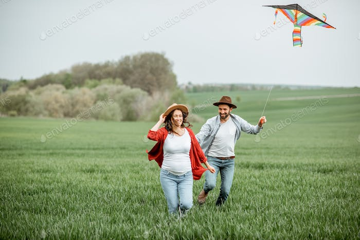 Lovely couple with kite on the greenfield