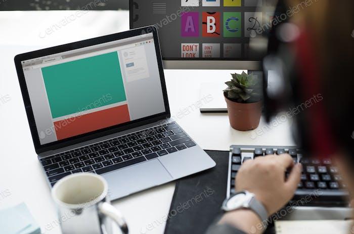 Laptop Screen Showing Desktop on Whtie Table beside Working Man