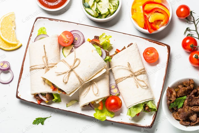 Burritos tortilla wraps with beef and vegetables on white