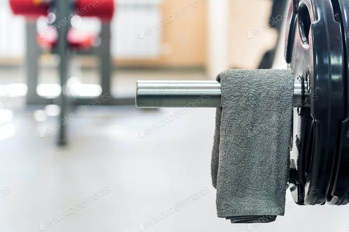 Grey towel hangs on barbell in gym