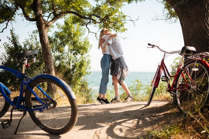 Young cute couple spending time together with red and blue classic bicycles beside