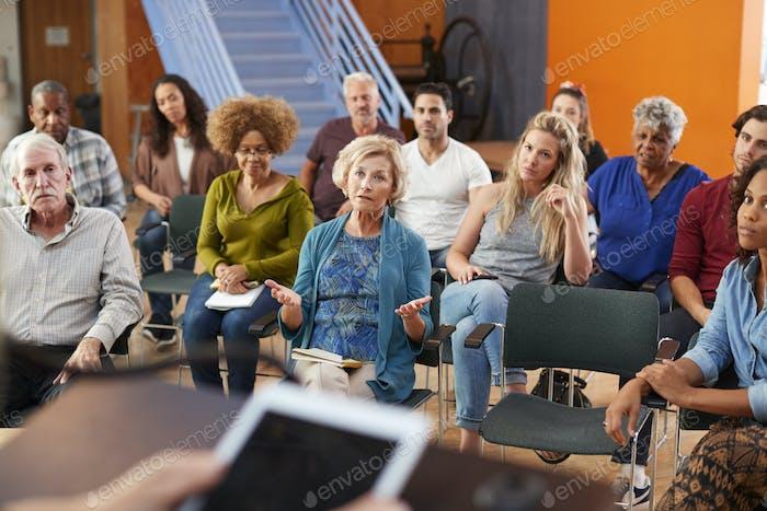 Frau spricht bei Gruppennachbarschaftstreffen im Community zentrum
