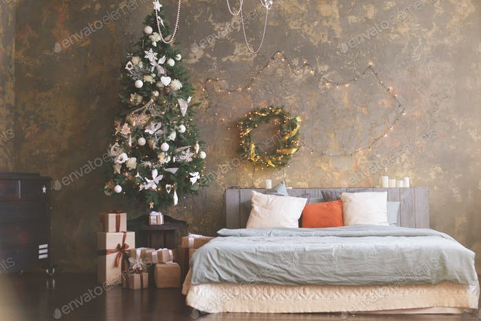 Christmas tree with a white bed in a white room
