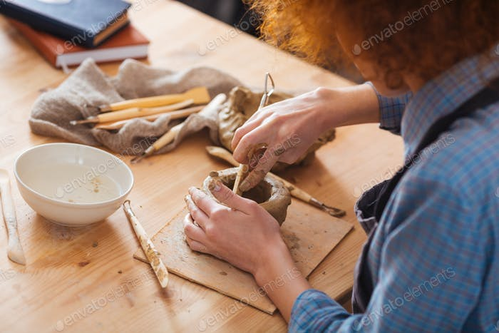 Concentrated curly young woman working on clay pot