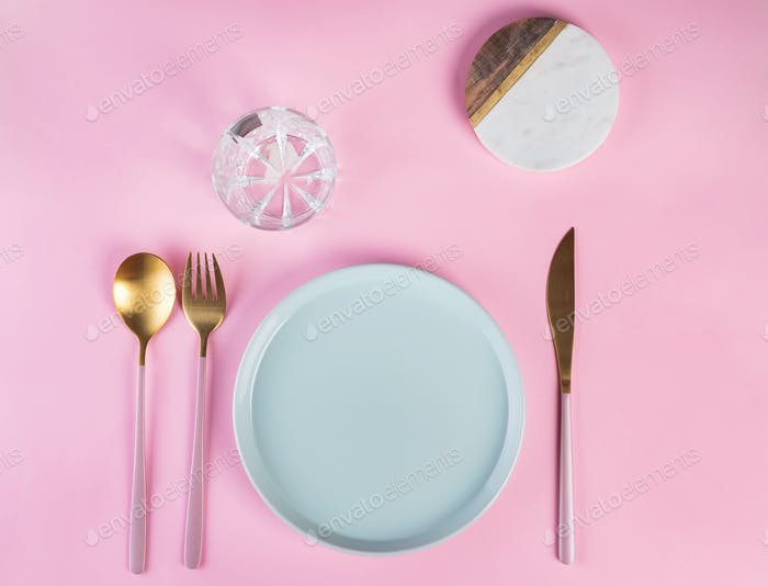 New luxury Golden cutlery with glass, blue plate on pink background. Top view. Pink knife and fork