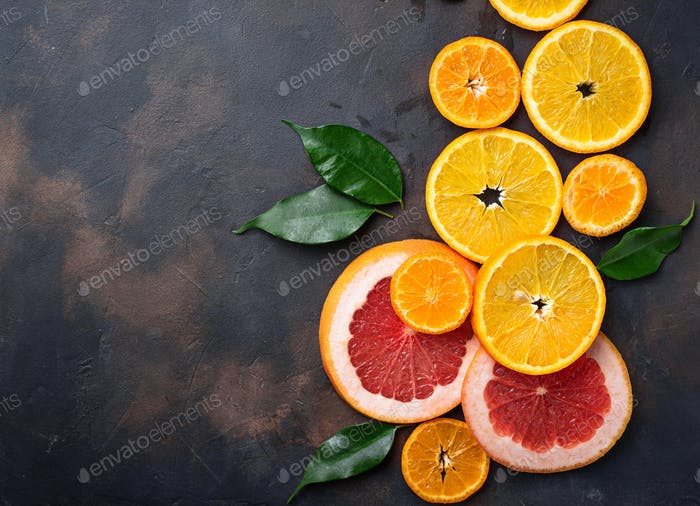 Different sliced citrus on dark concrete background