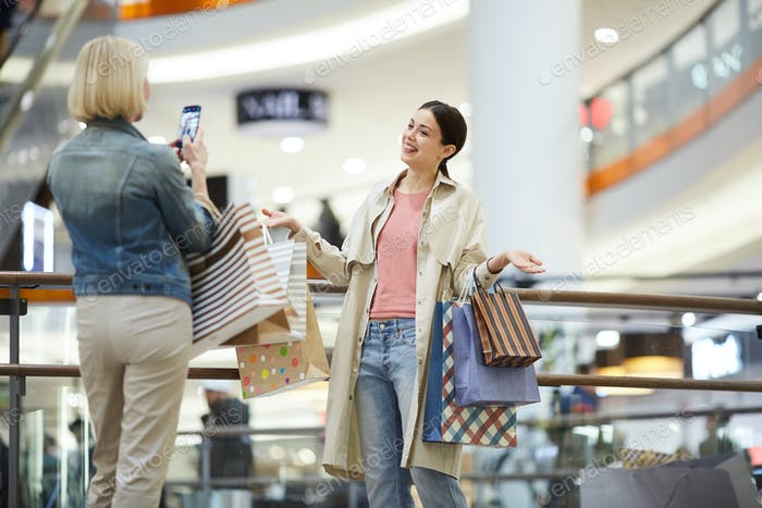 Lady photographing friend with plenty shopping bags