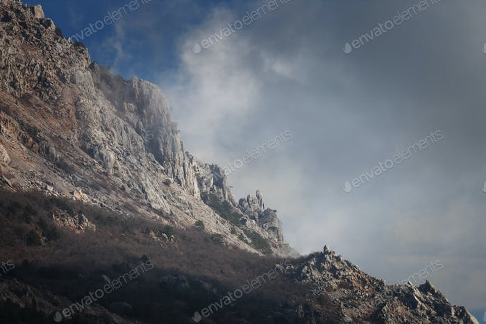 Slope mountain with scattered stones on a background of blue sky
